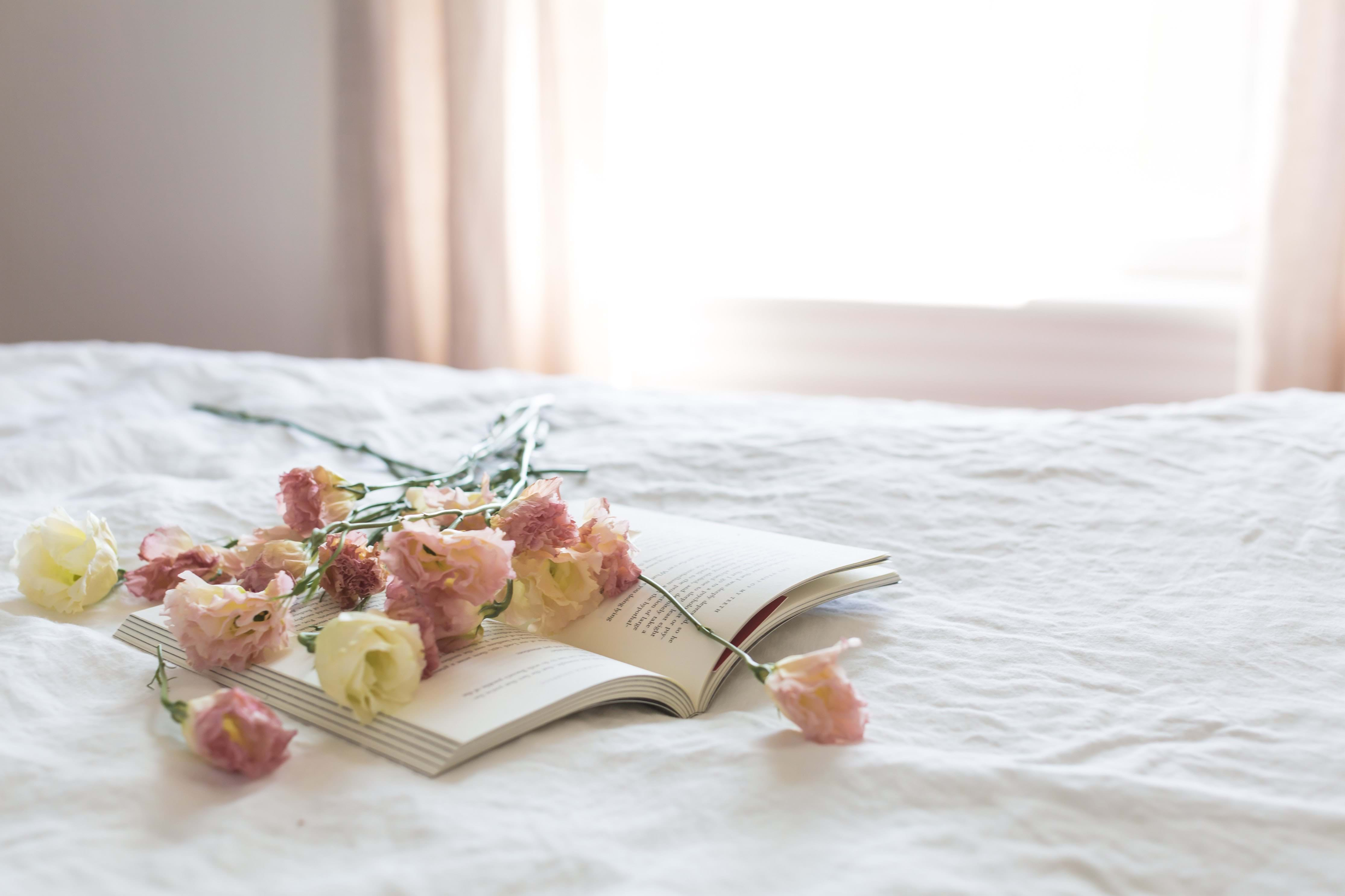 Flowers laying on a book in a bedroom